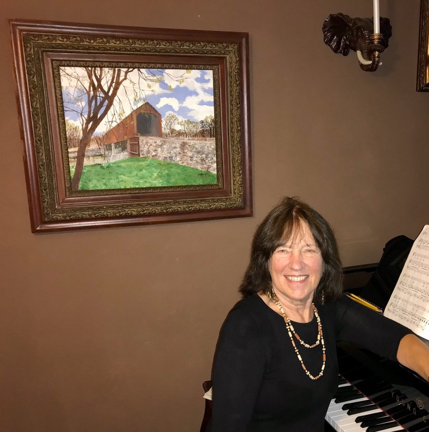 Sandy Day is seen with her painting of a covered bridge in Tyler State Park. Also an opera singer, Sandy has been president of the Delaware Valley Opera Company for the past 20 years.