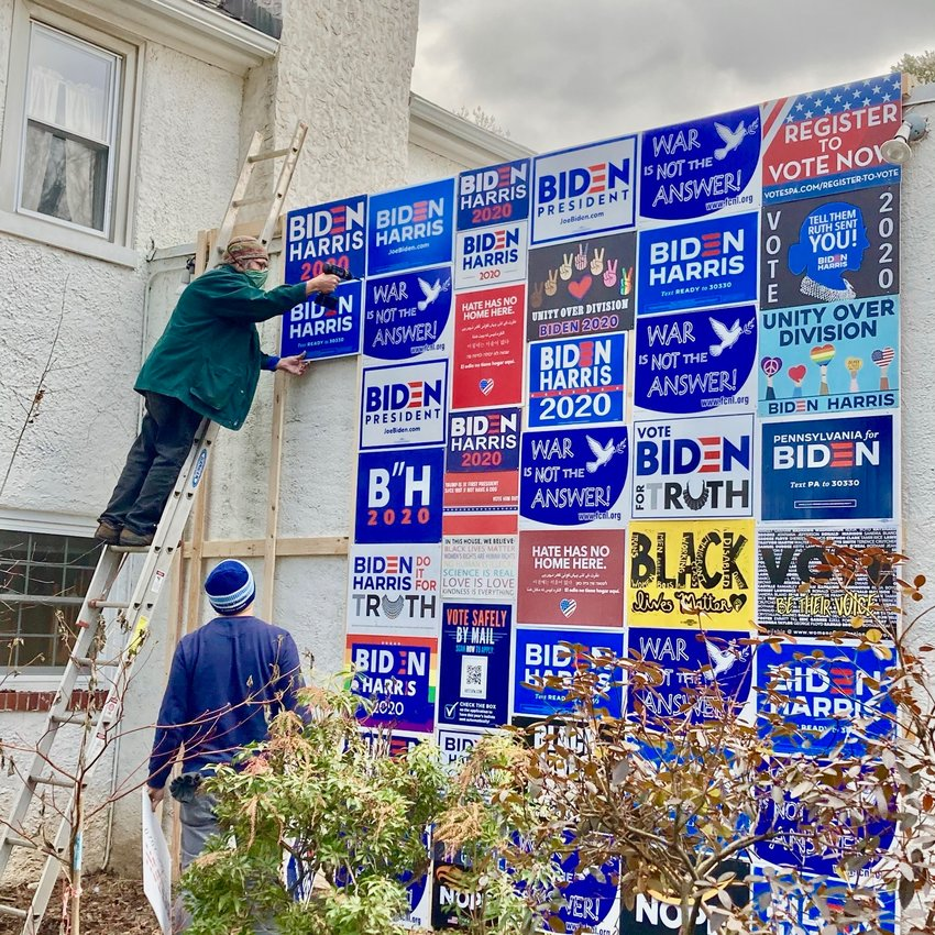 """Mt. Airy residents Clifford Wagner (on the ladder) and Mario Zucca help to construct the """"Blue Wall"""" at 258 W. Gorgas Lane in Mt. Airy. (Photo by Josephine Winter)"""