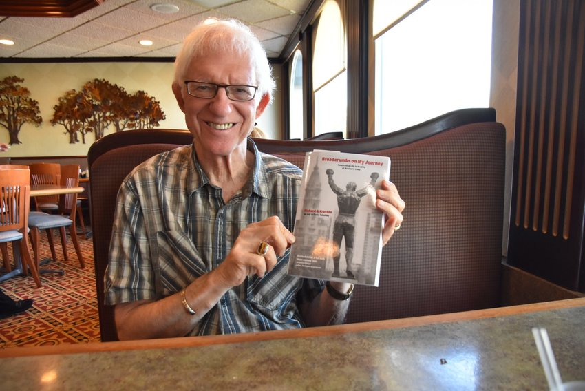 """Rich Krassen holds up his memoir, """"Breadcrumbs on My Journey,"""" written in his late 70s before he was diagnosed with stage 4 pancreatic cancer. (Photo reprinted, with permission, from the Northeast Times)"""