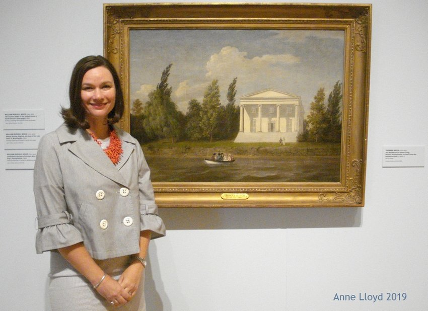"""Dr. Anna O. Marley, PAFA's Curator of Historical American Art, stands next to Thomas Birch's """"The Residence of James Craig, Bristol, Pennsylvania"""" (1820-21) (Photo by Anne Lloyd)"""