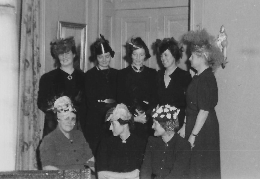 """Wearing their finest """"vegetable hats"""" at the home of Mrs. Ann Steele, of """"Sugarloaf"""" (now Chestnut Hill College's Sugarloaf Hill campus) in December 1939 are Wissahickon Garden Club members including Mmes. Butterworth, Gribbel, Lovering, Paul, Whitney, Johnson and Chase. Photo courtesy of the Chestnut Hill Conservancy."""