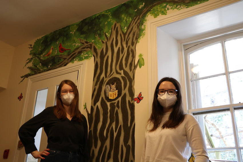 Maddie Megargee and Anna Kane next to the new mural at Hilltop Book. (photo by Hannah Lebowitz-Lockard)