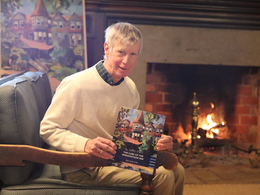 """Paul Hines, a former Middle School history teacher at Springside Chestnut Hill Academy, holds up a copy of his new book, """"The Lure of the Wissahickon Inn."""""""