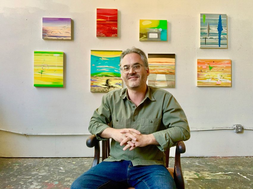 Eckel sits in front of some of his paintings now on exhibit at Awbury Arboretum in Germantown until June 30. (Photo by Noah Marmar)