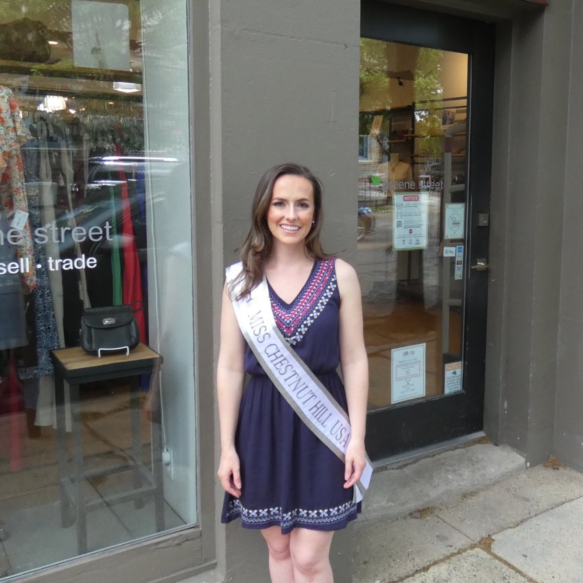 Kimberly Szabo poses in front of Greene Street on Germantown Avenue. The consignment shop provided her dress.