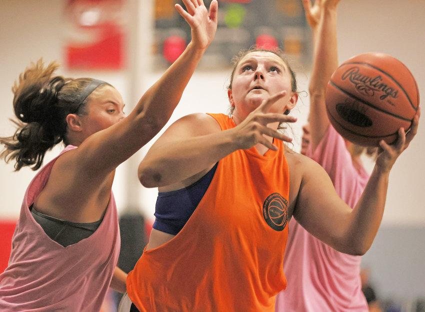 Brianna Hewlett of Team Orange, a Chestnut Hill College senior, gets off a lay-up while avoiding a defender.  (Photo by Tom Utescher)