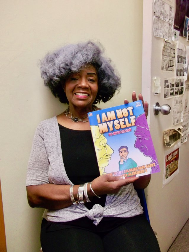 """""""Miss Lillian"""" Clark, who has lived in both East and West Mt. Airy over the last 55 years, proudly holds up her just-published coloring book, """"I Am Not Myself,"""" designed to teach children about Alzheimer's disease. (Photo by Len Lear)"""