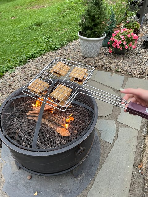 Most everyone cooks up s'mores when they're gathered around a firepit. But if you have a wood-burning model, you can stoke up some charcoal and make the entire dinner.