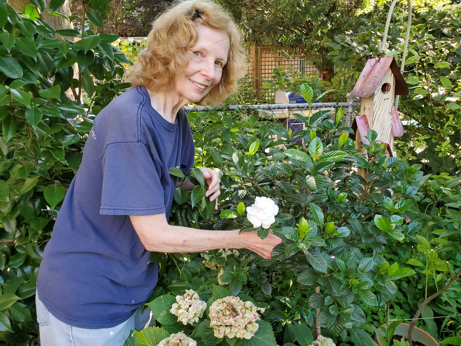 Valerie and a gardenia – part of her predictable garden.