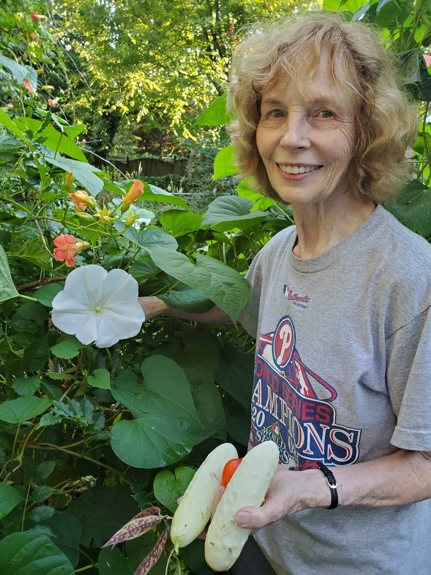 Valerie with a moon flower, trumpet vine, cucumbers and a tomato.