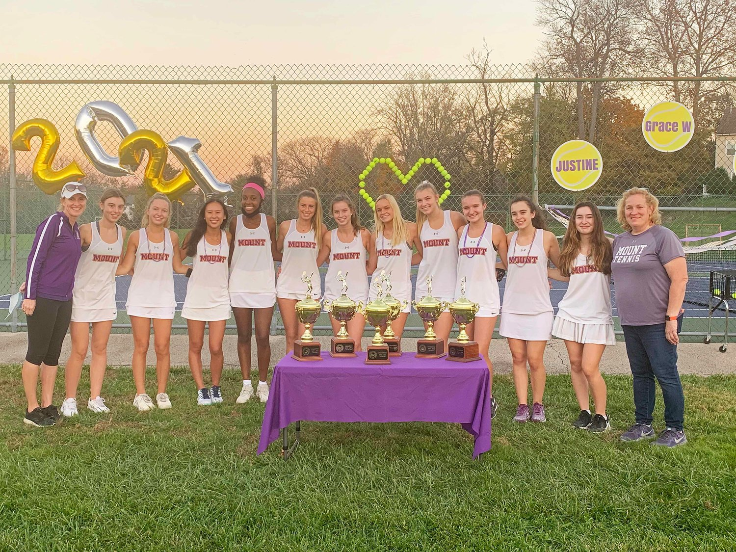 Mount St. Joseph's varsity tennis players gather around the league championship trophies they've won in each of the last six seasons.
