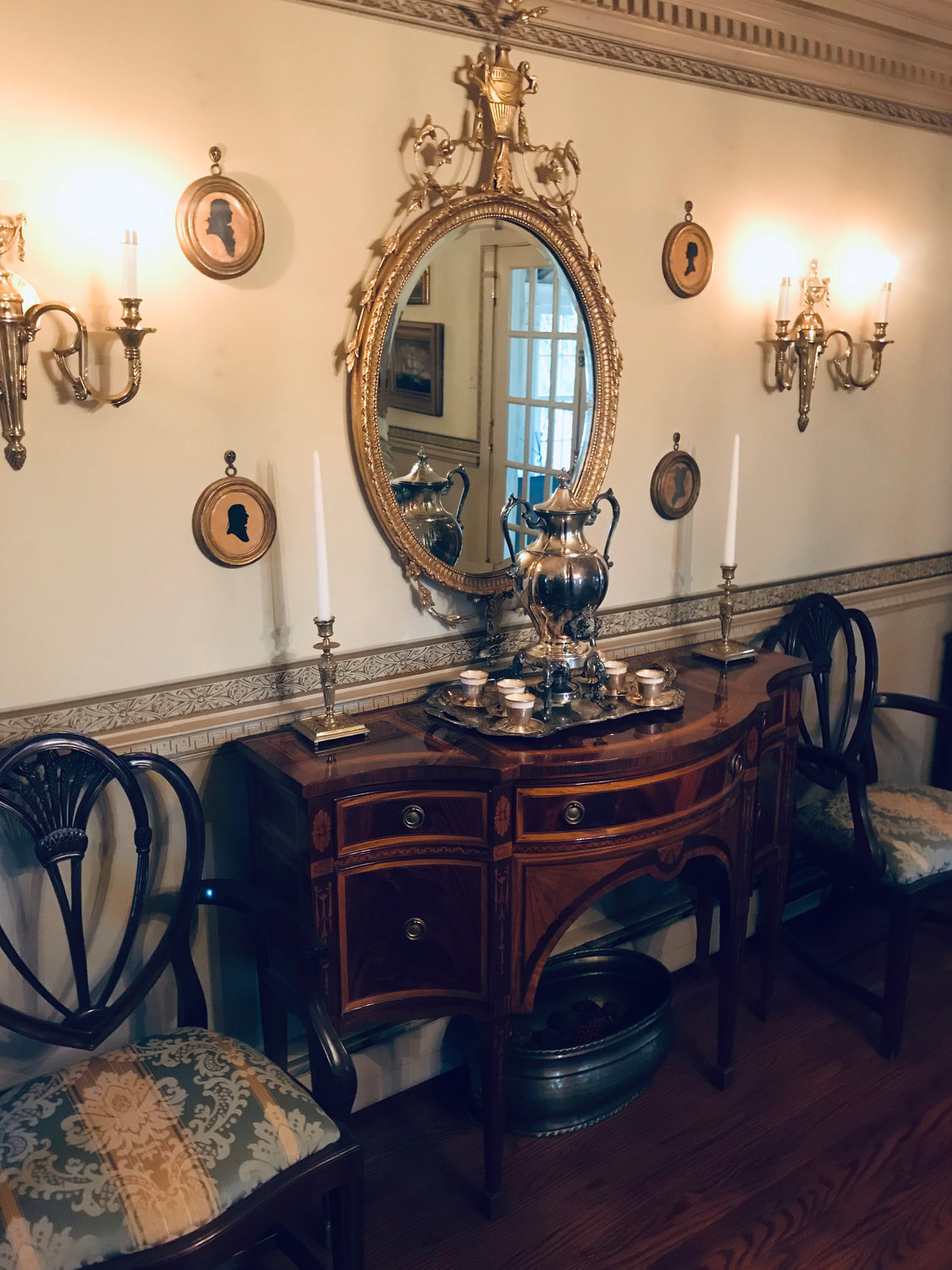 Signatures of a  dining room furnished in a Federal style: heart-shaped shield-back chairs, in- laid mahogany sideboard, and a gilded ormolu mirror displaying an urn surrounded by scrolls and husks.