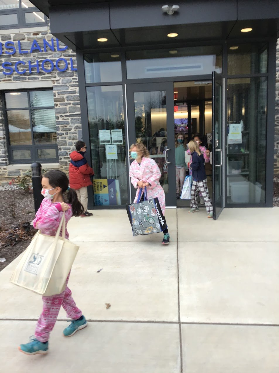 Lower School girls carry bags filled with collected goods for volunteer parents to deliver to the St. Vincent de Paul Food Pantry in Germantown.