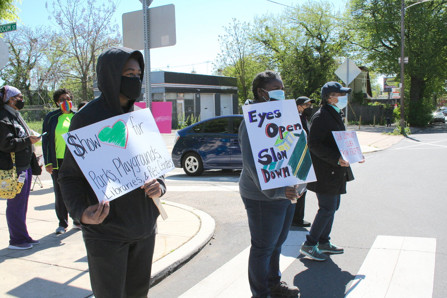 Tajae Faxon, Carla Bell, Evonne Tisdale, and other neighbors demonstrated in front of the Pleasant Playground Recreation Center, May 1, calling for a stop to the proposed development at 6717 Chew, which is visible in the background. They claimed the development will hurt the neighborhood and the playground and will worsen already bad traffic concerns outside the recreation center. (Photo by Patrick Cobbs)