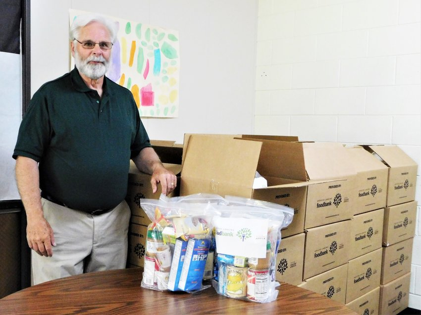 Mike Haley stands with one of two large stacks of packaged food bundles that will be distributed to Harrison Middle School students for take-home as a way to help provide for their nutrition needs.