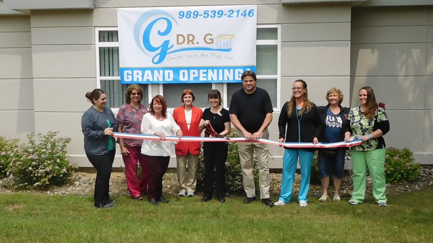 """Dr. """"G"""" (Maureen Gierucki, DDS) is joined Monday, July 8 by staff, family and friends, as she cuts the ribbon on her new dental office at 780 W. Spruce St. in Harrison."""