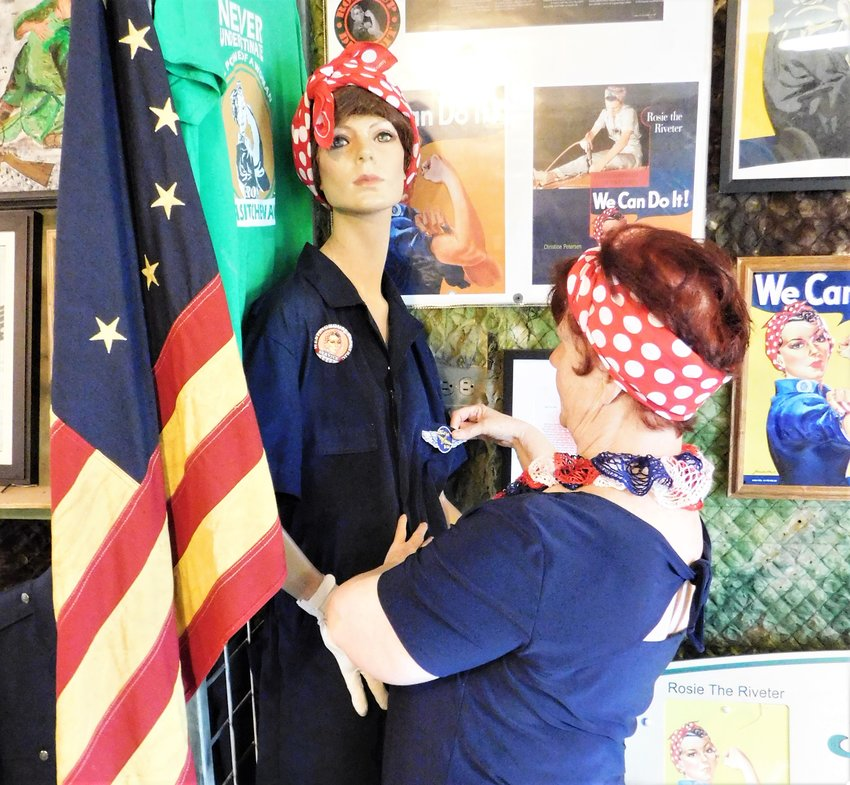 """In these photos, Maye Tessner-Rood sits on the bench created for her by the City of Harrison, and pins a winged Willow Run Bomber Plant patch on the display's Rosie mannikin. Also shown is a copy of the 1950 Patriotic Tide signed by Naomi Parker Fraley whose photo inspired the Westinghouse Electric """"We Can Do It"""" campaign. The photo of Charles Willits, who also played a part in the Willow Run Bomber Plant story, accompanies his uniform at the Veterans Display."""