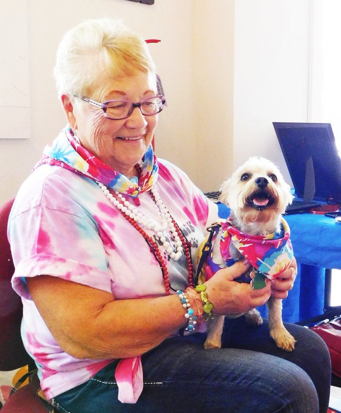 Betty Sprague holds Dusty, her Yorkie-poodle cross, Saturday during WOOFSTOCK. Dusty was another of the adoption success stories that result from the diligent efforts of the Clare County Animal Shelter.
