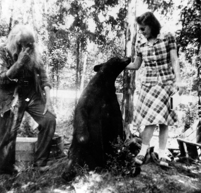 A visitor to Spikehorn's Wildlife Park gets friendly with a pet bear in the 1950s as Spikehorn looks on (left).
