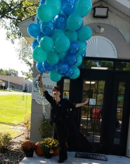 Harrison dentist Maureen Gierucki poses in a lighthearted moment in front of her new office.