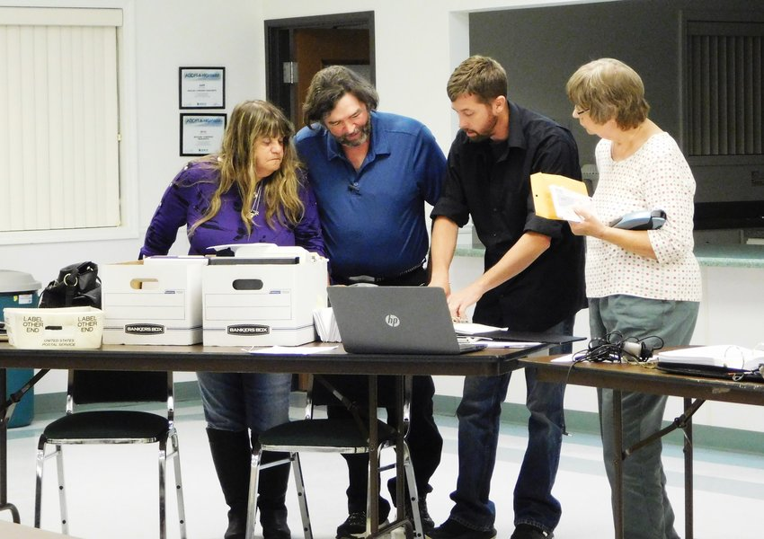 Chris Martin, resigned Redding Township treasurer, goes over the ledgers and other items which have been put in order prior to his departure from the board. Pictured, from left, are Nancy and Bruce Scarbrough, Martin and Marlene McGlashen.