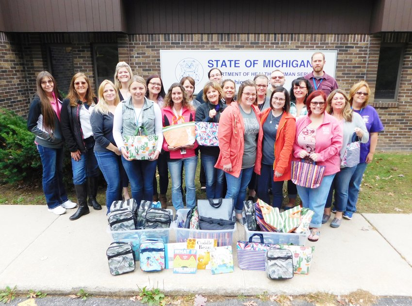 MDHHS staff gather around to accept the donation of insulated lunch bags filled with books and school supplies, one for each of the county's children in foster care.