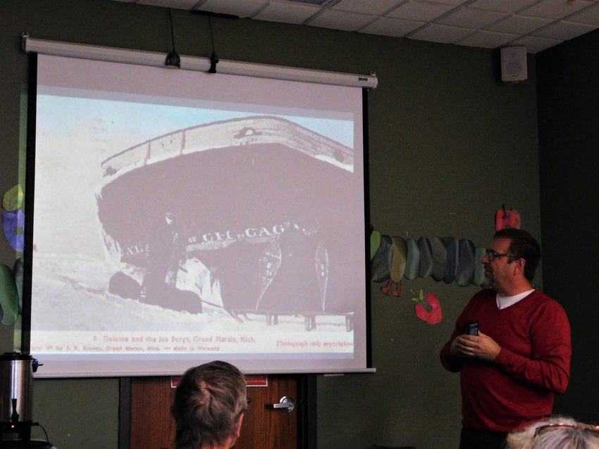 Ric Mixter, far right, shows a slide of the Galatea trapped in Lake Superior's ice at Grand Marais, Michigan.