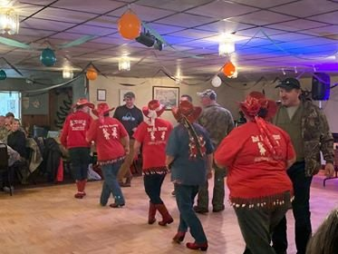 The Red Hat Strutters, a local dance group, attempts to teach a few redneck gentlemen to line dance.