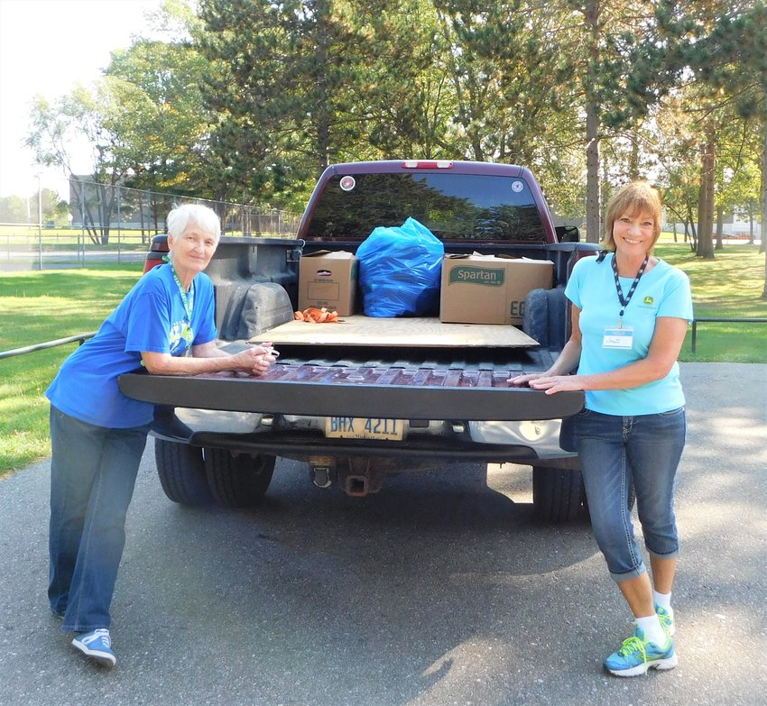 Marian Spencer, left, and Janet Cawood stand by a partial truckload of clothing and shoes collected for Hope Lutheran Church's free clothes closet in Farwell during the 2017 Harrison-Hayes Township Recycling Day held at Harrison City Park.