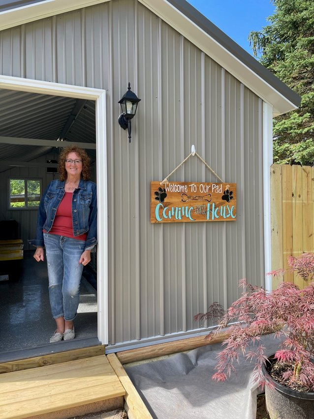 Deborah Kramp stands in the doorway of her new business the Canine Guest House LLC. The business opened recently and is accepting cats and dogs for pet boarding.