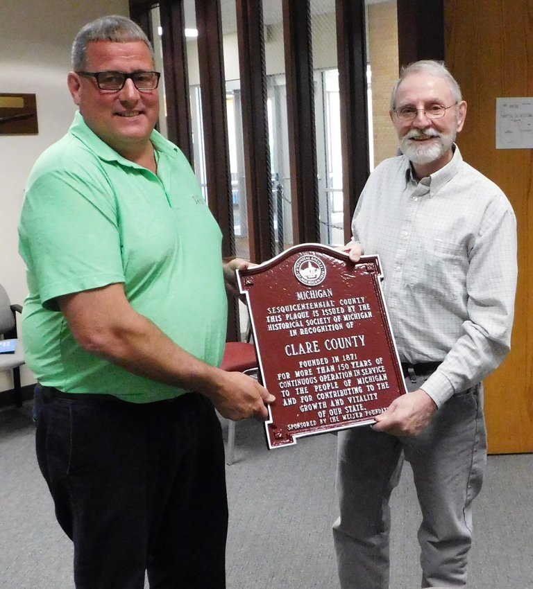 BOC Chairperson Jeff Haskell is shown here June 16 accepting a plaque honoring the county's 150 years from Lee Wixom on behalf of the Clare County Historical Society. The plaque is intended to hang in the Clare County Courthouse.