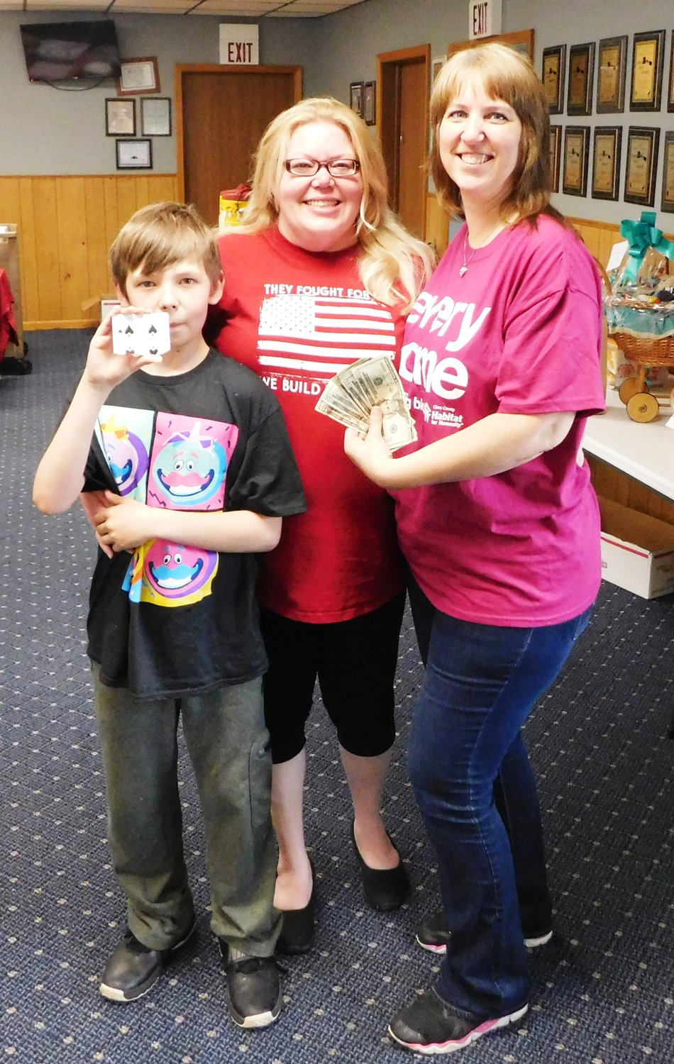 Lori Martin is pictured with 50/50 winners Beth Detzler and son James Monroe Pressley holding their half of the lucky 7 of clubs.
