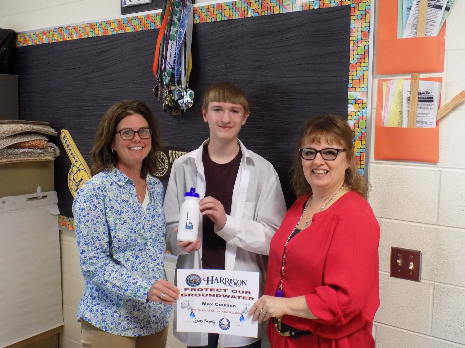 Joddie Gould, left, and Tracey Connelly, right, award Max Coulson his certificate as winner of the Water Bottle Design Contest held at Harrison Middle School.