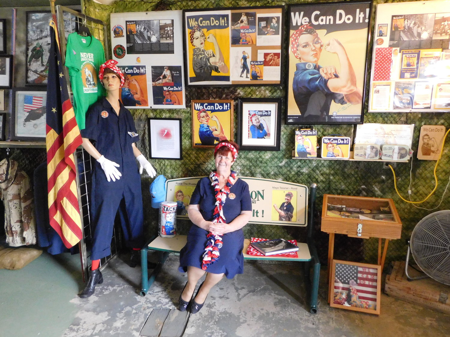 "In these photos, Maye Tessner-Rood sits on the bench created for her by the City of Harrison, and pins a winged Willow Run Bomber Plant patch on the display's Rosie mannikin. Also shown is a copy of the 1950 Patriotic Tide signed by Naomi Parker Fraley whose photo inspired the Westinghouse Electric ""We Can Do It"" campaign. The photo of Charles Willits, who also played a part in the Willow Run Bomber Plant story, accompanies his uniform at the Veterans Display."