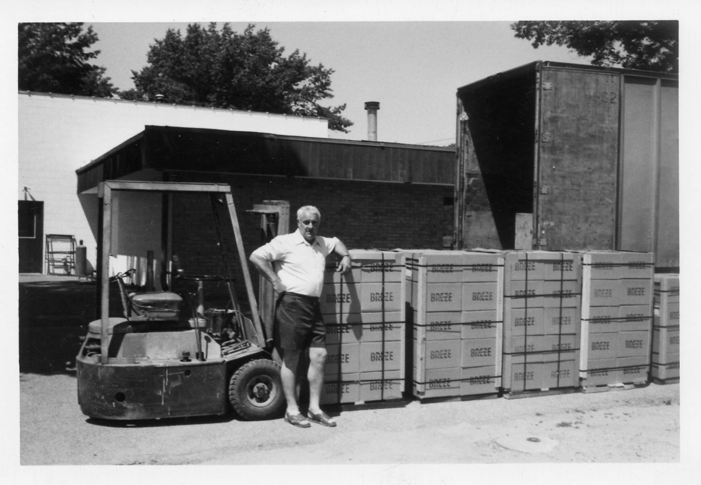 Nelson Reinke pauses for a photo with pallets of the Chimney Breeze stove pipe fan that was one of several of his business ventures during his ambitious career of self-employment.