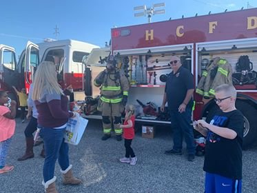 Chief Chris Damvelt and members of the Harrison Community Fire Department display and explain their gear and equipment to families.