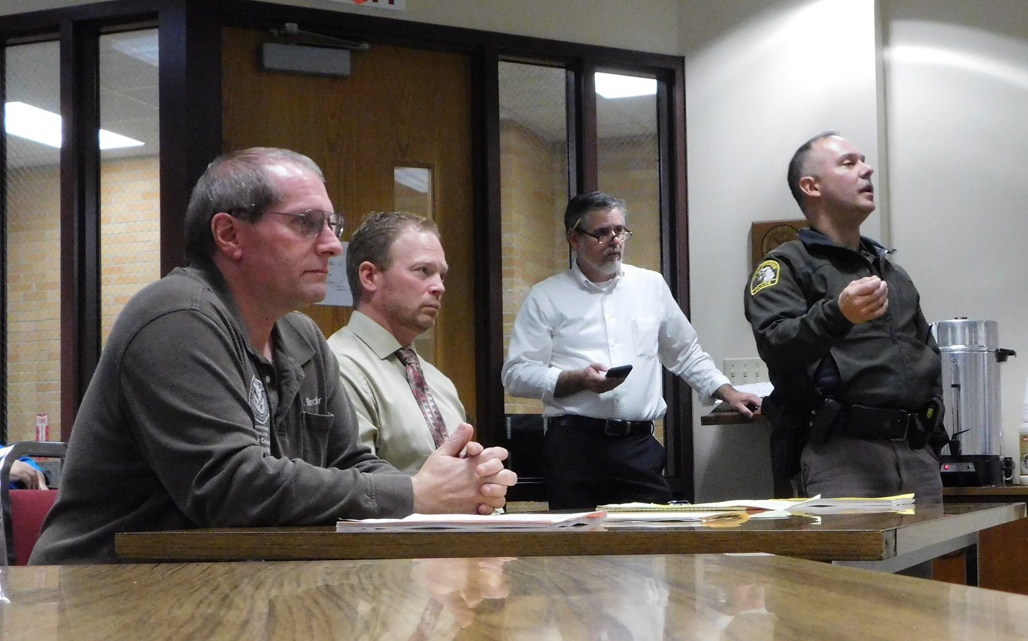 Pictured during the Oct. 16 meeting of the Clare County Board of Commissioners are, from left: Jerry Becker, Emergency Management director; District Court Judge Joshua Farrell; and Peter Preston, Equalization director – listening as Undersheriff Dwayne Miedzianowski describes the now commonplace occurrence of total security screening at schools, governmental and law enforcement buildings.