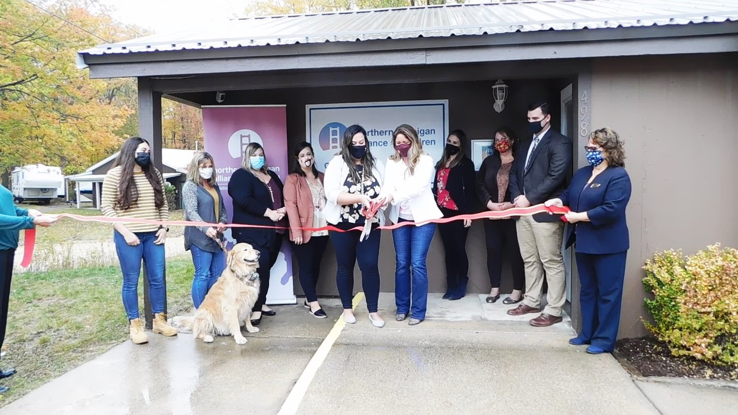 At center, Eriana DeKalita-Mull, left, and Mandy Wigren officially cut the ribbon marking the official opening of the Northern Michigan Alliance for Children's Center for Hope and Healing. They were joined by NMAC staff and representatives from the Harrison Chamber of Commerce.