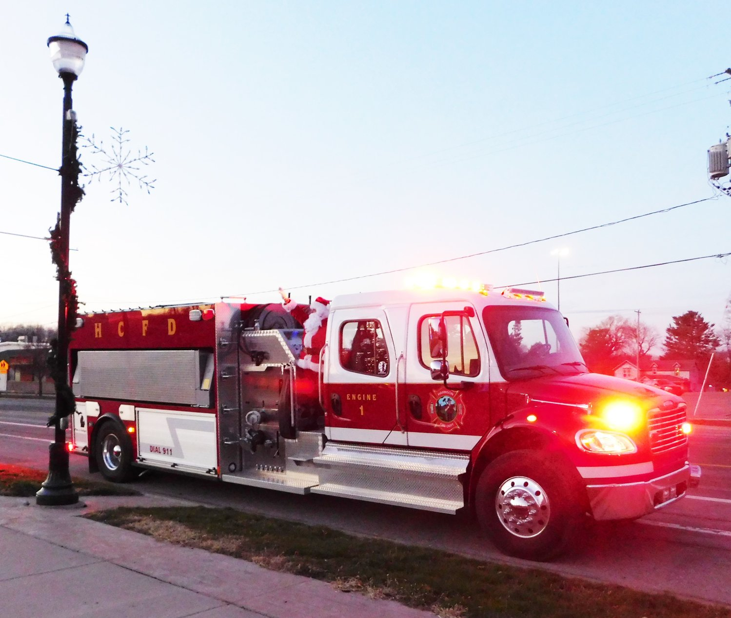Arriving at the Harrison Town Square in style aboard a fire engine, Santa waves to all the children and adults gathered to ring in the holiday season.