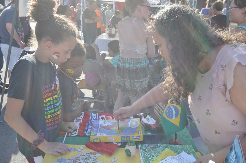 Ivette de Assis-Wilson shows a map of Brazil to Brandon and Jozy Hudson Saturday during Humans United for Equality's Celebration of Unity at Pike Place. Countries around the world were represented at the festival.