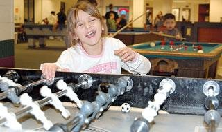Kaiglynn Harvey laughs after missing the ball while playing a game of Foosball with a friend at the Crawfordsville Boys and Girls Club.