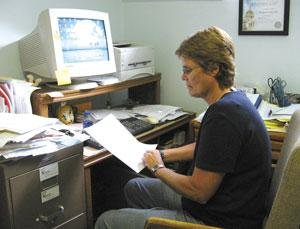 CASA program manager Jane Christophersen checks a file of a child in need of a special advocate. She is seeking volunteers to serve in that role.