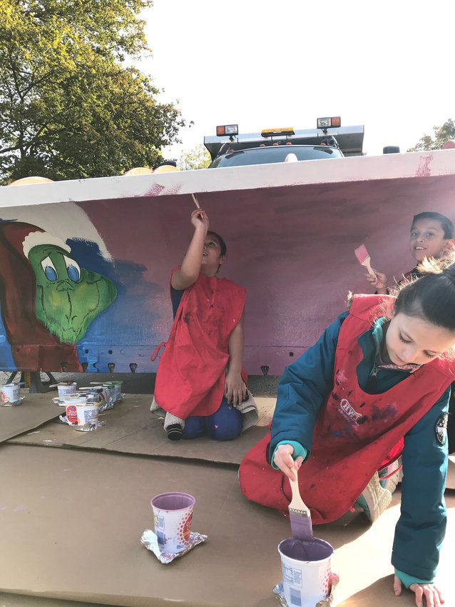 Yoselyn Gomez Castro, first from left, Briellah Grimes and Joel Conde Pascual paints a plow.