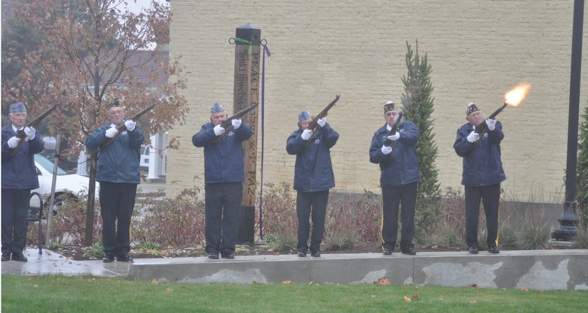 Members of the Crawfordsville American Legion Byron Cox Post 72 Honor Guard conduct a 21-gun salute Monday during the community Veterans Day ceremony at Pike Place.