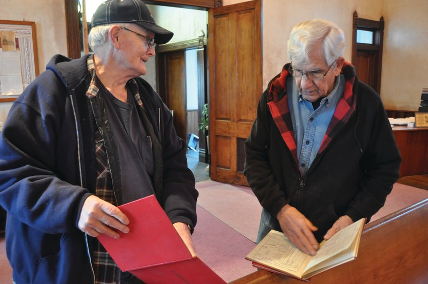 Bill Glover, left, shows Don Cumbow name listed in an attendance book for Osborn Prairie Christian Church. The men's families attended the church.