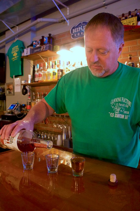 Brett Cating, owner of The Canning Factory Bar & Grill in Ladoga, practices his pouring technique Wednesday ahead of a speakeasy transformation set to take place Friday and Saturday.