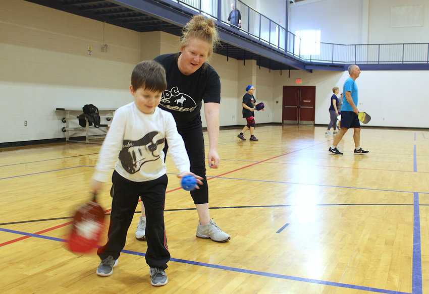Dominique Fruits takes a moment to teach the finer points of Pickleball to son Noah, 4, Friday at Crawfordsville Parks and Recreation.