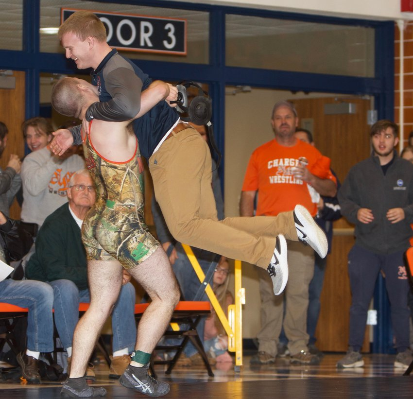 North Montgomery senior Dawson McCloud picks up Charger wrestling coach Bryce McCoy after he punched his ticket to the regional final with come-from-behind win over Carmel's Garrett Sharp.