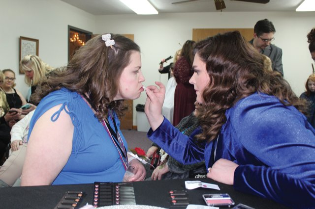 Edith Cline, left, has lipstick applied by Hair and Makeup station stylist Erin Harper on Friday at New Hope Christian.