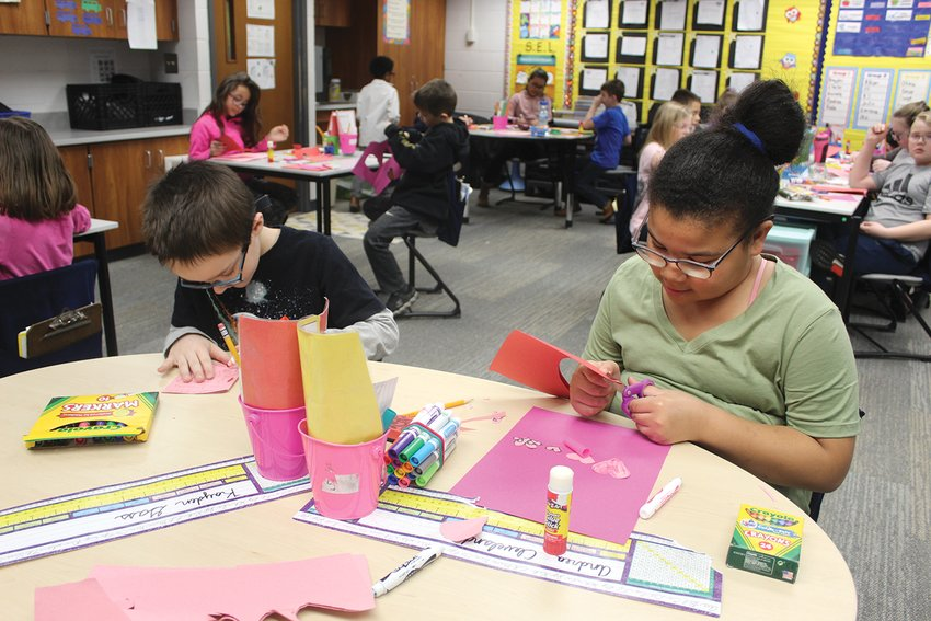 Nicholson third graders Kayden Gass, left, and Andrea Cleveland work together to make Valentine